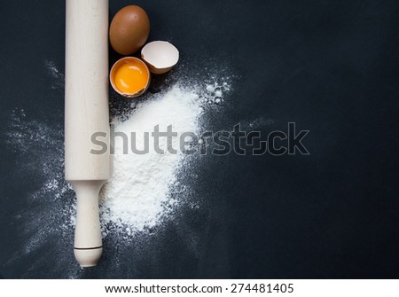 Rolling pin, flour and eggs on black background