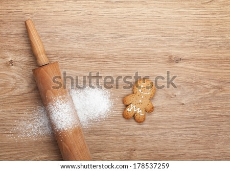 Rolling pin with flour and gingerbread cookie on wooden table. View from above - stock photo