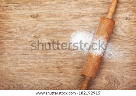 Rolling pin with flour on wooden table. View from above - stock photo