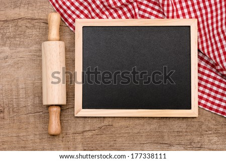 rolling pin with slate on wood - stock photo