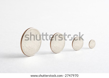 Rolling quarters are getting smaller. Impression of diminishing value of money. - stock photo