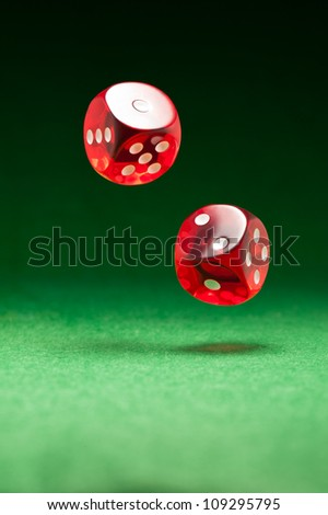 Rolling red dice over green surface - stock photo
