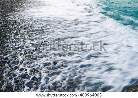Rolling sea waves breaking along the coast. Waves blurred long exposure. - stock photo