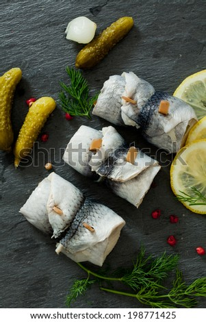 Rollmops - pickled herring fillets over the wooden board - stock photo