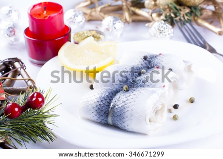 Rollmops with lemon for Christmas on a plate - stock photo