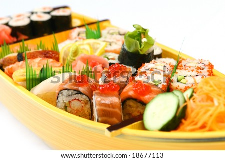 Rolls and sushi at the traditional japan boat - stock photo