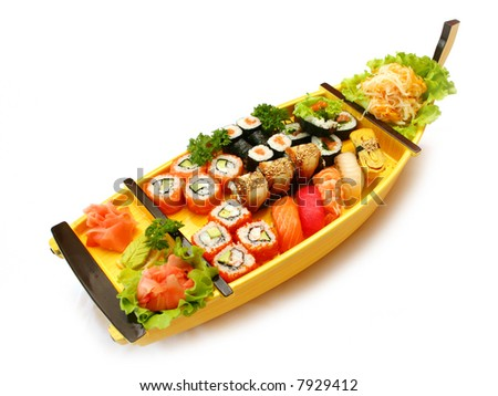 Rolls and sushi at the traditional japan boat on white background - stock photo