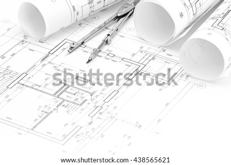 rolls of architectural blueprints and floor plan with drawing compass - stock photo