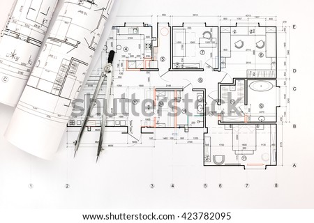 rolls of architectural blueprints and technical drawings with drawing compass - stock photo