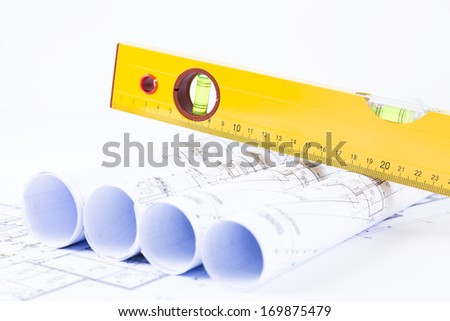 rolls of architectural projects and plans with yellow level on top