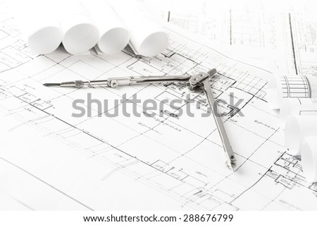 rolls of architecture blueprints and house plans on the table and drawing compass - stock photo