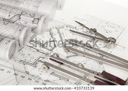 rolls of architecture blueprints, house plans &  compasses - stock photo