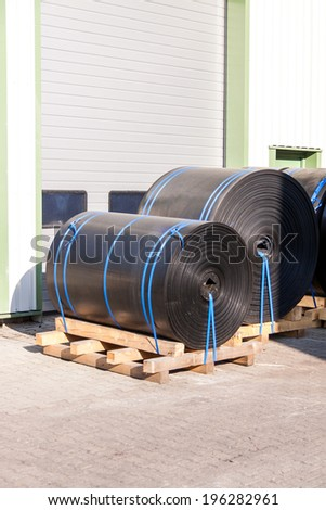 Rolls of black industrial plastic tied to wooden pallets outside a warehouse or factory for use as waterproofing in building and construction - stock photo