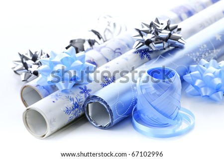 Rolls of Christmas wrapping paper with ribbons and bows - stock photo