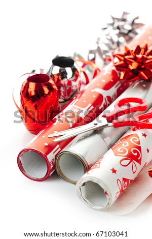 Rolls of Christmas wrapping paper with ribbons, bows and scissors - stock photo