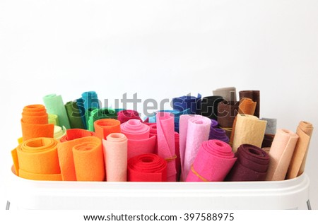 Rolls of colored felt standing in the box. Background white.
