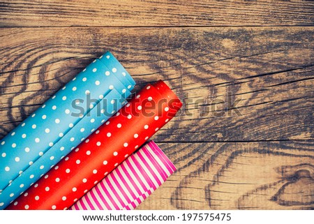 Rolls of colored wrapping paper on wooden background  - stock photo