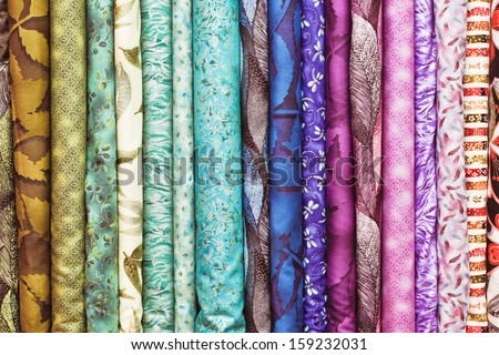 Rolls of colorful fabric as a vibrant background image - stock photo