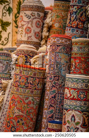 Rolls of Colorful Persian Rugs stacked in a Corner of a Store. - stock photo