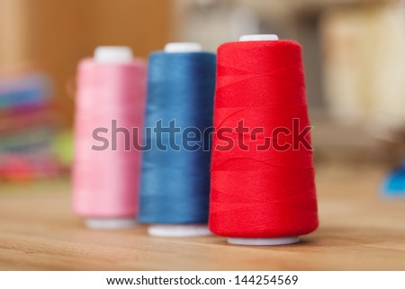 Rolls of colorful sewing thread or yarn standing upright in an oblique row on a wooden counter top with shallow dof - stock photo