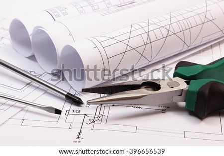 Rolls of diagrams, metal pliers and screwdriver on electrical construction drawing of house, work tool and drawing for projects engineer jobs, concept of building house - stock photo