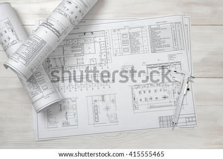 Rolls of drawing sketches lie on a wooden surface. Top view compositin. Workplace of architect or constructor. Engineering work. Construction and architecture. Architect drawing. Exact calculation.