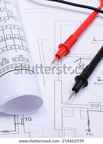 Rolls of electrical diagrams and cables of multimeter lying on construction drawing of house, drawings and tools for engineer jobs - stock photo