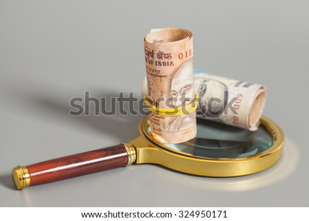 Rolls of Indian Currency Rupee Notes on magnifying glass isolated on gray - stock photo