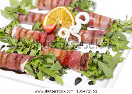 rolls of meat and greens on a white background in the restaurant
