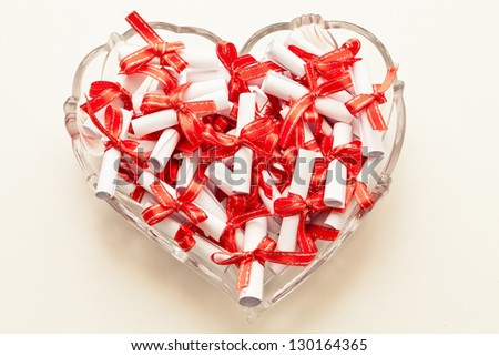 rolls of paper tied with a red ribbon in the shape of heart - stock photo