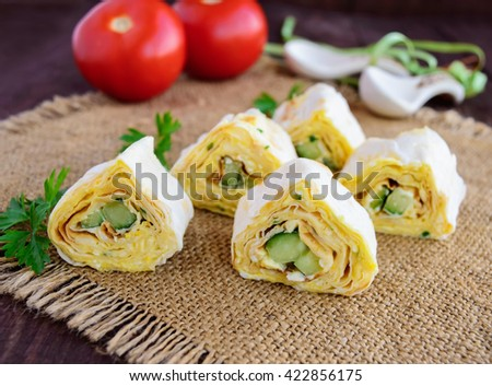Rolls of pita with cheese and cucumber on a wooden background - stock photo