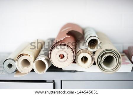 Rolls of wallpaper on desk - stock photo