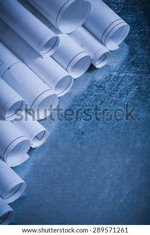 Rolls of white blueprints on scratched metallic background vertical version construction concept. - stock photo