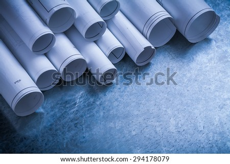 Rolls of white construction drawings on scratched metallic background building and architecture concept. - stock photo