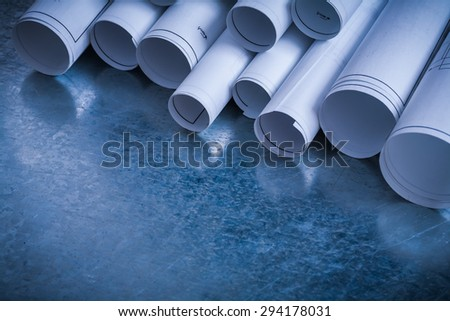 Rolls of white construction plans on scratched metallic background building and architecture concept. - stock photo