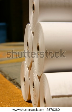 Rolls of white newspaper printing paper on a loading dock ready for delivery