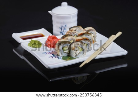 Rolls with eel on black with reflection - stock photo