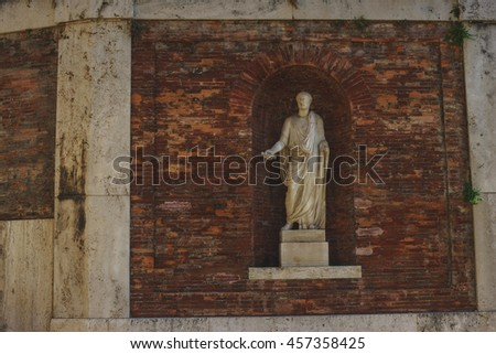 Roma, Italy - July, 2016: Detail of a wall and an ancient statue in a niche on the streets of the old city of Rome.
