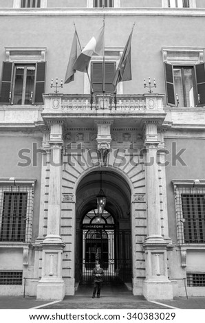Roma, Italy - October 2015:  Italian carabiniere policeman guards the entrance at a public institution in a historic building Fondazione con Sud in Rome with the flags of Italy and the European Union - stock photo