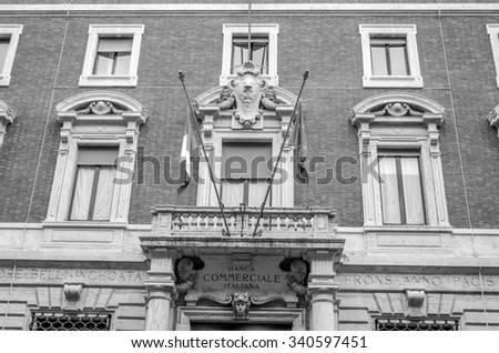 Roma, Italy - October 2015:  Windows and doors on the old historical building of a commercial bank with sculptures and ornaments in Rome on which hang the flags of Italy and the European Union - stock photo