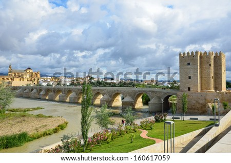 Roman bridge is over the Guadalquivir river in Cordoba. It was built by the Romans in the early 1st century BC and restored several times. - stock photo
