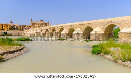 Roman bridge is over the Guadalquivir river in Cordoba. The Calahorra Tower (Torre de la Calahorra) is a fortified gate to protect the bridge. - stock photo