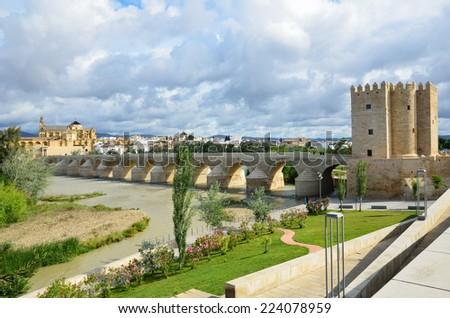 Roman bridge is over the Guadalquivir river in Cordoba. The Calahorra Tower (Torre de la Calahorra) is a fortified gate to protect the bridge. - stock photo