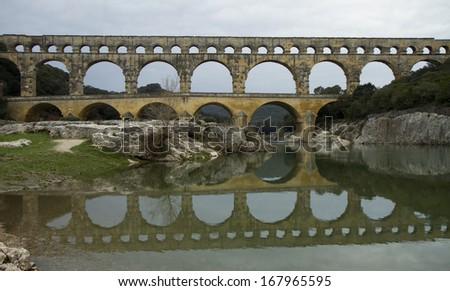 Roman Bridge with reflection in water - stock photo