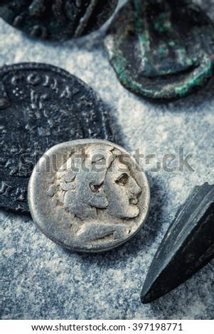 Roman coins and arrowhead on stone surface - stock photo
