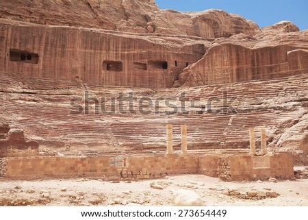 Roman-era amphitheater carved into the pink sandstone at Petra, Jordan. The building facades cut into the rock behind are ancient graves. - stock photo