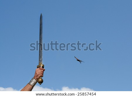 Roman Sword with golden Bird of Pray at the hilt is thrust skywards in victory with Bird of Pray swooping - stock photo