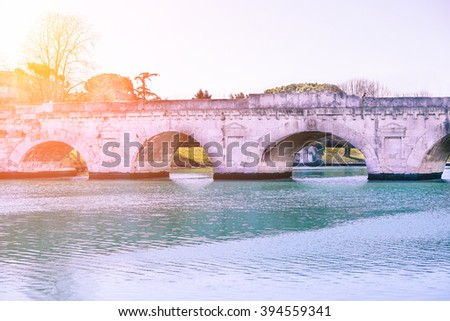 Roman Tiberius bridge built in the early 1st century BC across the Marecchia river in the Historic center of Rimini - Traveling around Italy concept - Soft rose quartz filter with artificial sunlight - stock photo