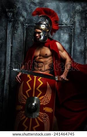 Roman warrior with muscular body holding sword and shield - stock photo