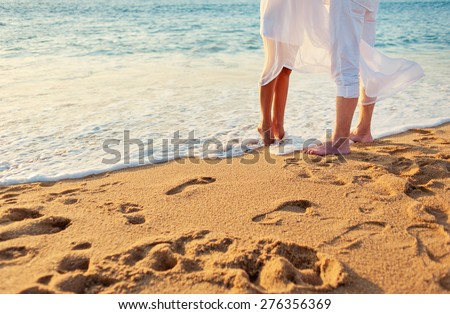 Romance concept. Honeymoon at the sea. Loving couple on the beach. Close up male and female feet on the sand. - stock photo
